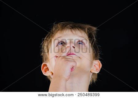 The boy picks his nose and looks up, against a black background stock photo