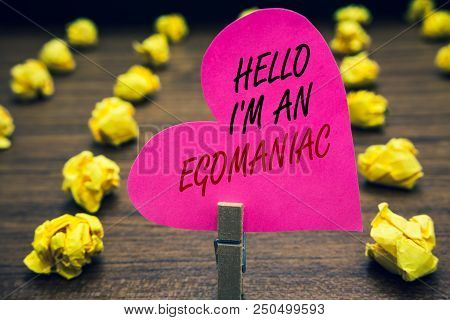 Conceptual hand writing showing Hello I am An Egomaniac. Business photo text Selfish Egocentric Narcissist Self-centered Ego Paperclip hold pink written heart woody floor with yellow lobs stock photo