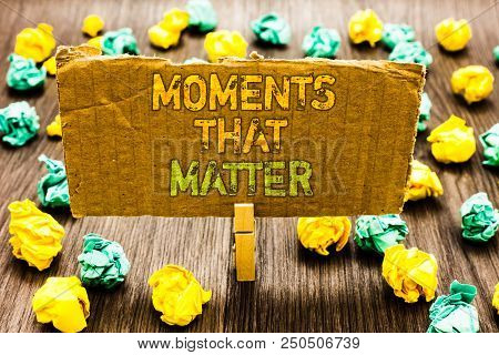 Text sign showing Moments That Matter. Conceptual photo Meaningful positive happy memorable important times Paperclip grip cardboard with texts many colorful lobs scattered on wooden desk stock photo