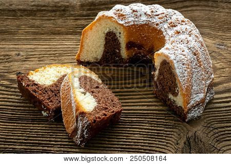 Traditional homemade marble cake. Sliced marble bundt cake on wooden table stock photo