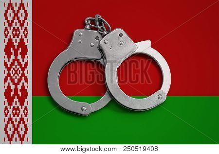 Belarus flag  and police handcuffs. The concept of observance of the law in the country and protection from crime. stock photo