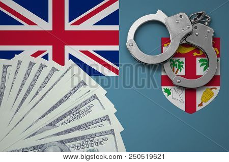 Fiji flag  with handcuffs and a bundle of dollars. The concept of illegal banking operations in US currency. stock photo