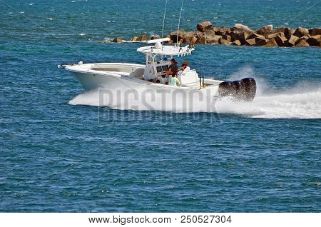 Fishing boat powered by three outboard engines exiting Government Cut in miami,Florida headed towards the open ocean. stock photo