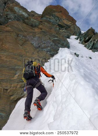 mountain climber on a steep climbing route on a north face in the Swiss Alps near Zermatt stock photo