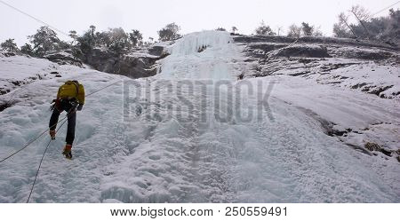 male mountain guide rappelling off a steep frozen waterfall after an ice climbing excursion stock photo