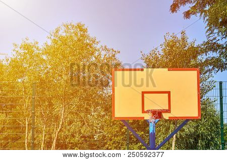 Close-up of a basketball hoop in public sport playground, sunlight effect. stock photo