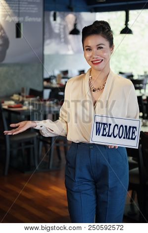 Gorgeous Asian female cafe manager holding white Welcome sign and pointing to side standing in restaurant on blurred background and looking at camera smiling stock photo