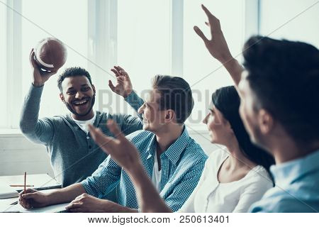 Students Playing with Rugby Ball in Classroom. Multiethnic Team. Indoor American Football. Rugby Player. Playing Together. Football Equpment. Friends in Classroom. Game in Classroom. stock photo