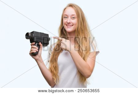 Blonde woman teenager filming holding super 8 video camera very happy pointing with hand and finger stock photo