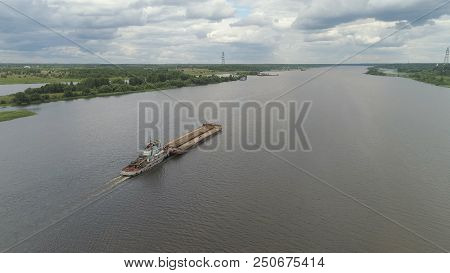 Aerial view:Barge with cargo on the river Volga. River tugboat moves cargo barge, Cargo ship on the river. stock photo