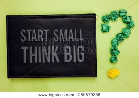 Word writing text Start Small Think Big. Business concept for Initiate with few things have something great in mind Green back black plank with text green paper lob form question mark stock photo