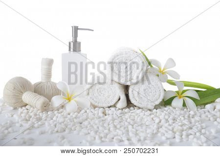 White frangipani with rolled towel ,bottle oil with herbal ball ,leaf on pile of white stones  stock photo