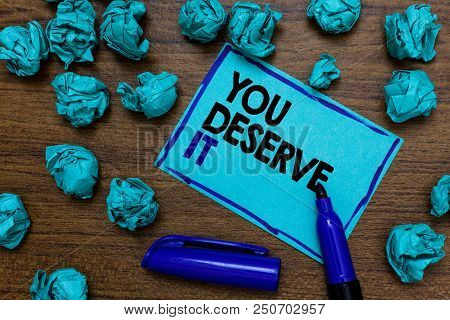 Conceptual hand writing showing You Deserve It. Business photo showcasing Reward for something well done Deserve Recognition award written blue letters on page blue marker and paper lumps stock photo