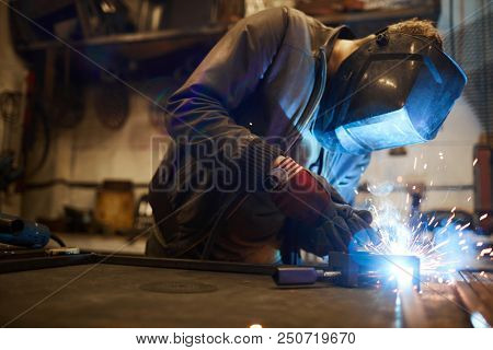 Young welder in protective mask leaning over workbench and welding iron workpieces stock photo