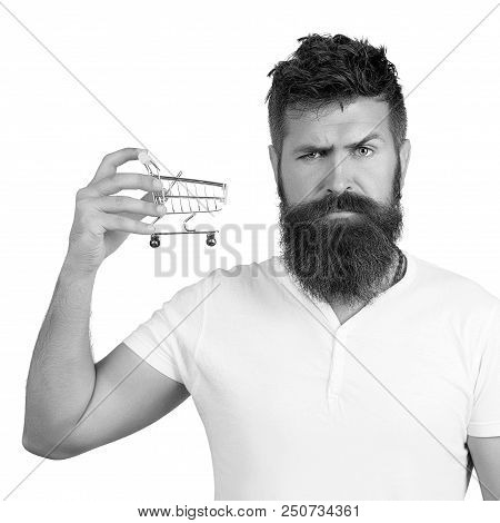 e-commerce and shopping concept. Bearded man wearing white t-shirt holding mini shopping cart on right hand. Closeup portrait of businessman showing mini shopping cart, online shop, ecommerce concept stock photo