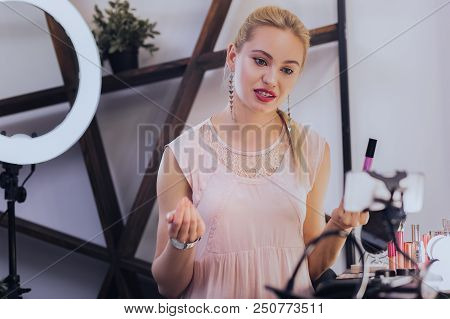 Makeup tutorial. Blonde-haired professional beauty blogger wearing beige blouse filming makeup tutorial stock photo