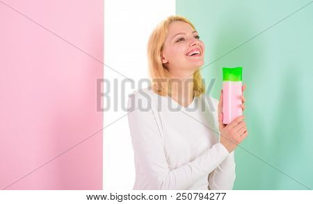 Expert tips achieve incredible hair. How repair bleached hair fast and safely. Girl blonde holds shampoo bottle. My hair care secret. Woman shows beauty product for hair. Beauty treatment product. stock photo