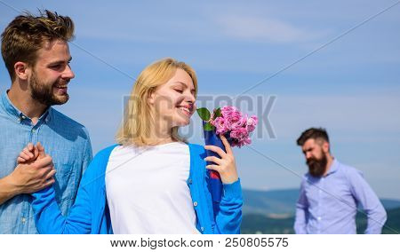 New love. Ex partner watching girl starts happy love relations. Couple in love dating outdoor sunny day, sky background. Ex husband jealous on background. Couple with flowers bouquet romantic date. stock photo
