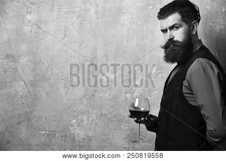 Degustator with glass of red wine. Sommelier with confident face drinks wine glass. Man with beard and mustache holds wine on beige wall background, copy space. Service and profession concept. stock photo