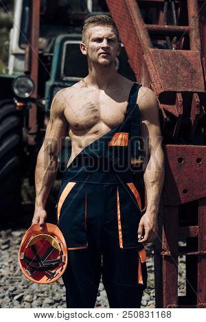 Metal worker. Metal worker rest at heavy machinery. Handsome metal worker in working uniform. Strong metal worker with muscular arms and torso. stock photo