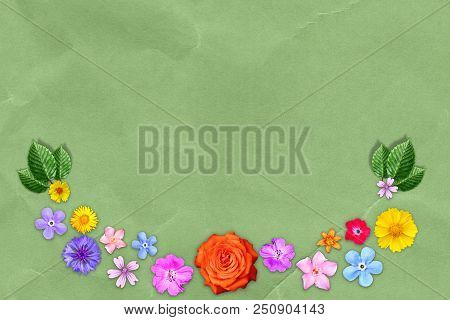 Beautiful decoration flowers frame with empty in center on green kraft paper background. stock photo