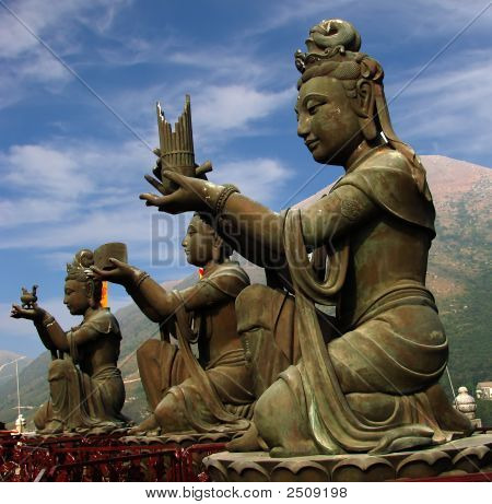 three statues for females offering different things in Buddha temple in Hong Kong stock photo