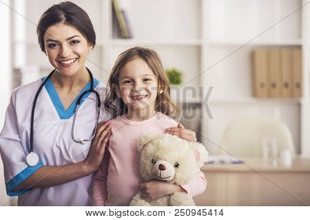 Friendly Doctor With Small Patient. Happy Girl And Doctor With Stethoscope. Joyful Nurse Plays With