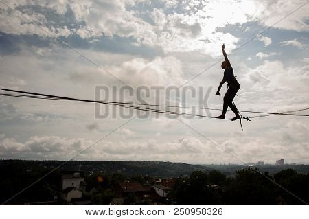 Young blondie woman walking on the slackline rope on the background of clear blue sky stock photo