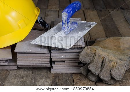 Helmet, tiles and tools for the builder. Accessories for construction workers on a wooden workshop table. Dark background. stock photo