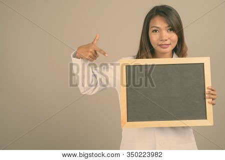 Portrait of Asian woman doctor against gray background stock photo