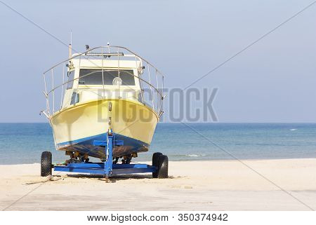 a yellow boat stands on a trailer on a sandy beach stock photo