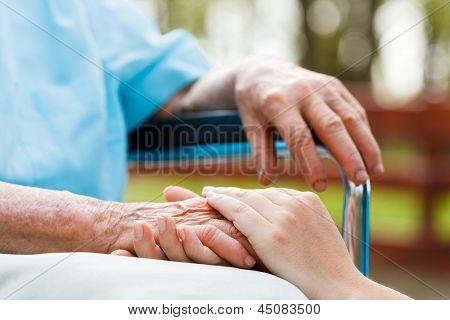 Young doctor hands holding the elderly lady's hand. stock photo