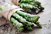 Bunch of crisp asparagus on wooden table