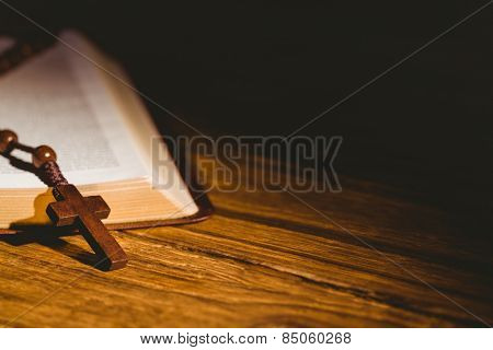 Open bible with rosary beads on wooden table stock photo