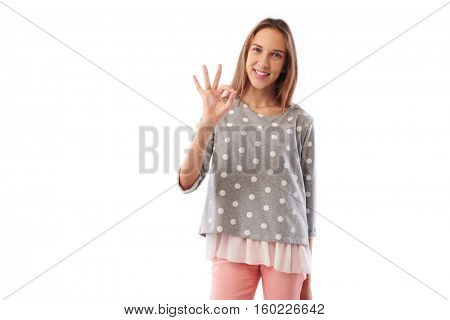 Mid shot of skinny happy toothy smiling young girl showing ok gesture standing over white background. Holding hand on hip while posing at the camera Concept of  nonverbal communication stock photo
