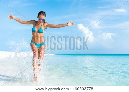 Sexy bikini body woman playful on paradise tropical beach having fun playing splashing water in free