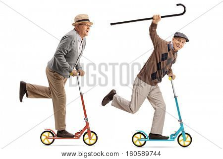 Full length portrait of two overjoyed seniors riding scooters isolated on white background stock photo