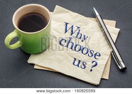 Why choose us? Handwriting on a napkin with cup of coffee against gray slate stone background stock photo