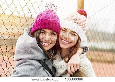 Two female besties in knit beanies and coats hugging and smiling. Two young best friends enjoying outdoors, loving and hugging each other. Vibrant color, natural light, medium retouch. stock photo