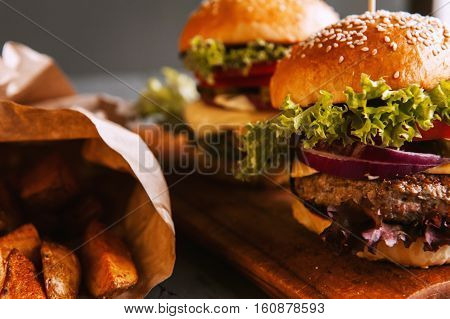 Two mouth-watering delicious homemade burger used to chop beef. on the wooden table. small white flags inserted in the burgers. stock photo