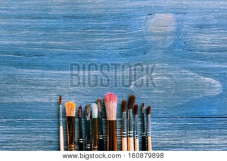 Row of artist paintbrushes closeup on artistic background. stock photo