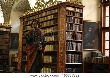A Late-Gothic wooden statue of St John the Evangelist at Strahov's monastery library in the Czech Republic. He's holding a small pouch called a girdle-book which served as a travel bag. stock photo