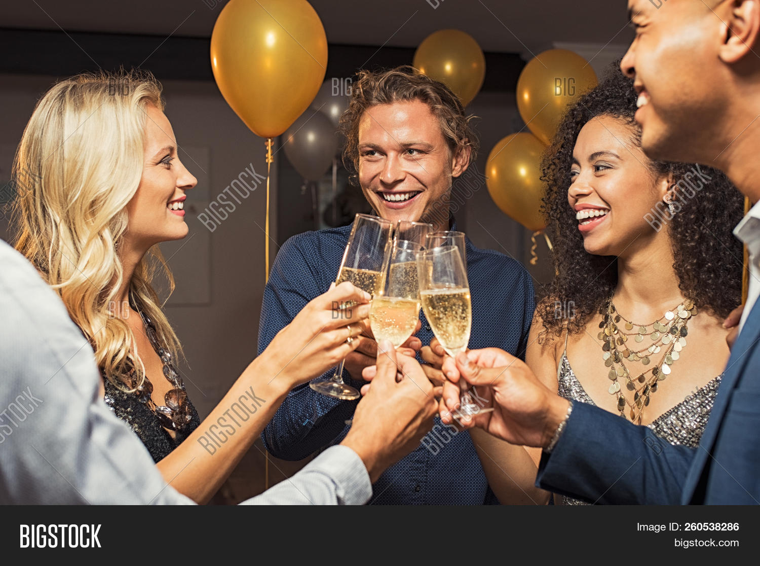 Group of young multiethnic friends toasting with champagne flutes to celebrate new year. Happy guys