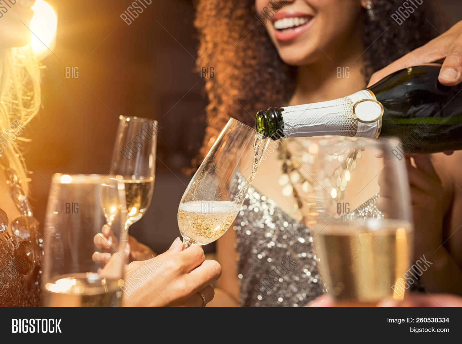 Hand pouring champagne from bottle into glasses with friends around him. Closeup of hand pouring whi