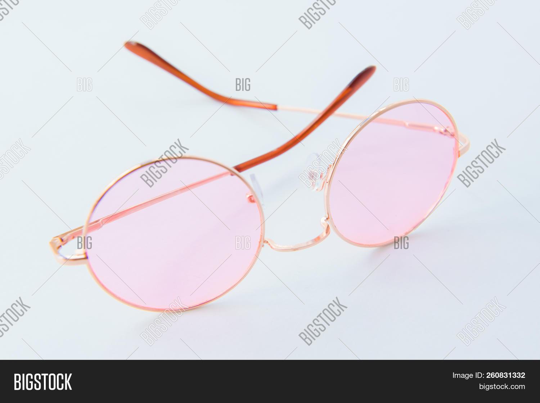 Round Italian sunglasses on white background. Pink eyeglasses. Modern protective eyewear shades. Eye UV protection accessories