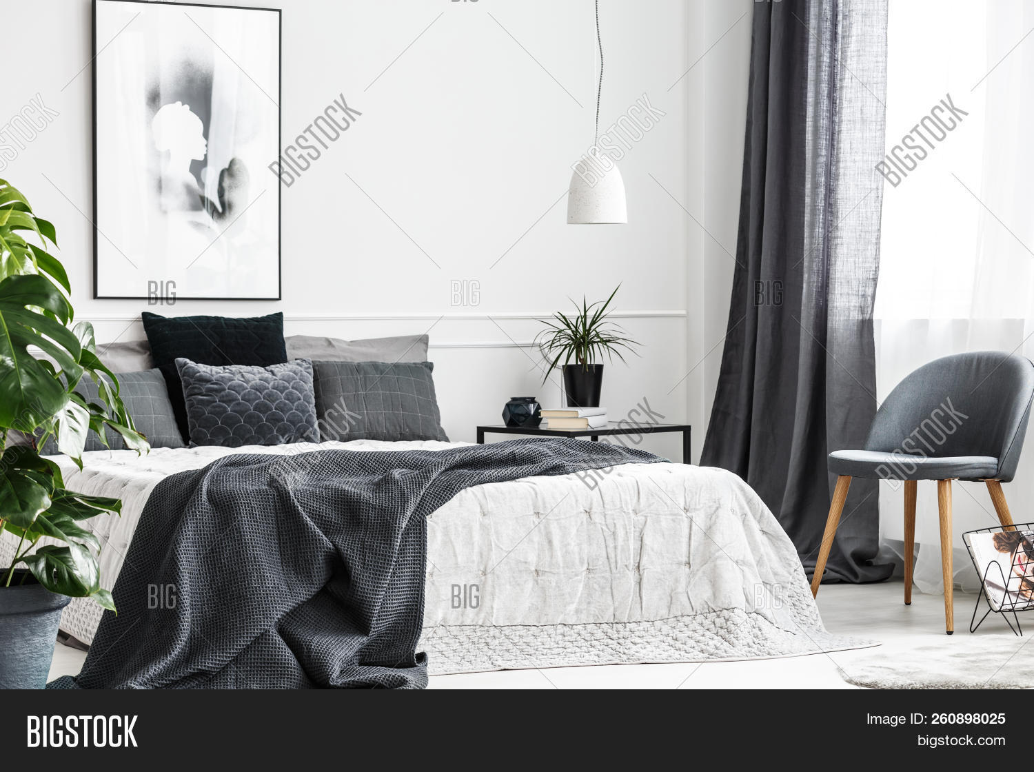 Modern, Gray Chair With Wooden Legs By A Window Of A Bright Bedroom Interior With A Dark Gray Blanke