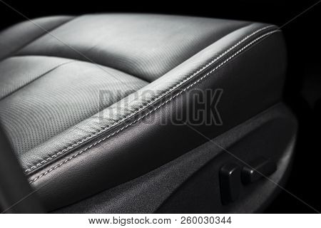 Modern luxury car black leather interior. Part of leather car seat details with stitching. Interior of prestige modern car. Comfortable perforated leather seats. Black perforated leather. Car detailing stock photo
