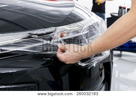 Car wrapping specialist putting vinyl foil or film on car. Protective film. Applying a protective film with tools for work. Car detailing. Transparent film. Car paint protection. Trimming. stock photo