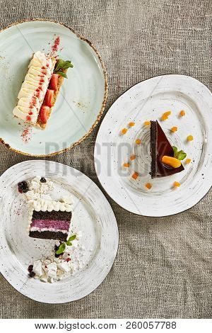 Triangular Slices of Berry Cakes and Chocolate Pie on Vintage Rustic Background Top View. Fruit and Berries Cheesecake, Apricot Brownie with Whipped Cream, Strawberries, Mint and Meringues stock photo
