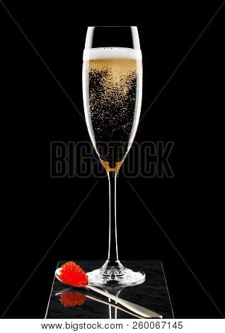 Elegant glass of yellow champagne with red caviar on golden spoon of caviar on marble board on black. stock photo